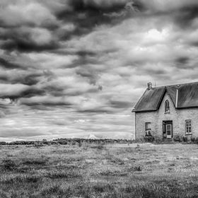 An abandoned farm house sits in the middle of a field while ominous skies loom overhead.