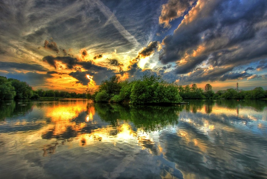 Sunset over one of the small islands in the lake behind Delapre Abbey, Northampton UK.  3 Shot HD...