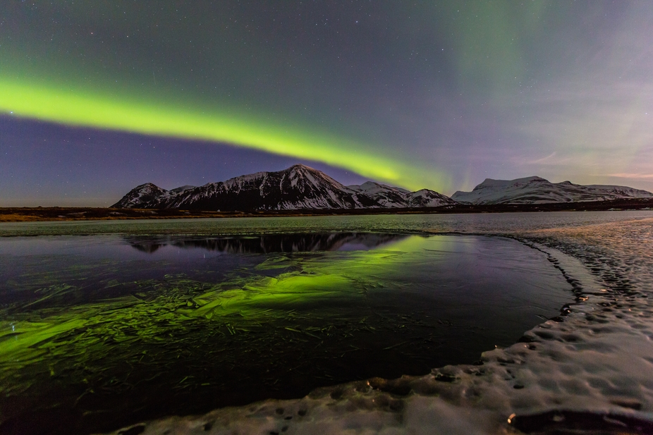 A small lake is freezing. The auroras are reflecting in the new fragmented ice on the surface