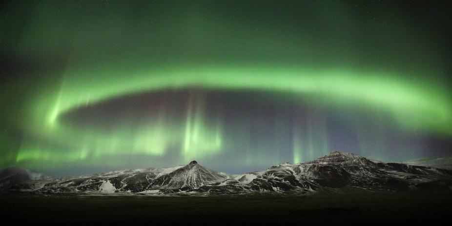 Beautiful Aurora circle over mountain Skardsheidi in Hvalfjordur, west part of Iceland