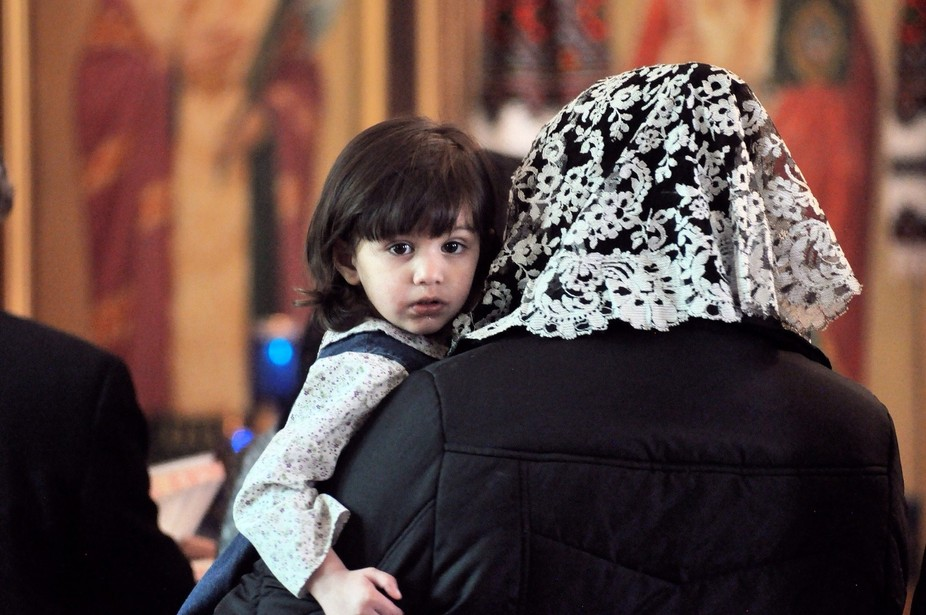 A young girl looking over her mothers shoulders during a prayer services for the people in the Uk...