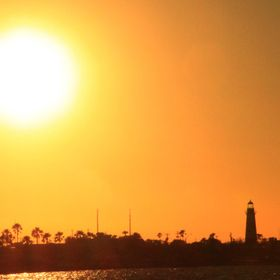 The sun setting over Port Isabel, Texas with a lighthouse in view as a silhouette.