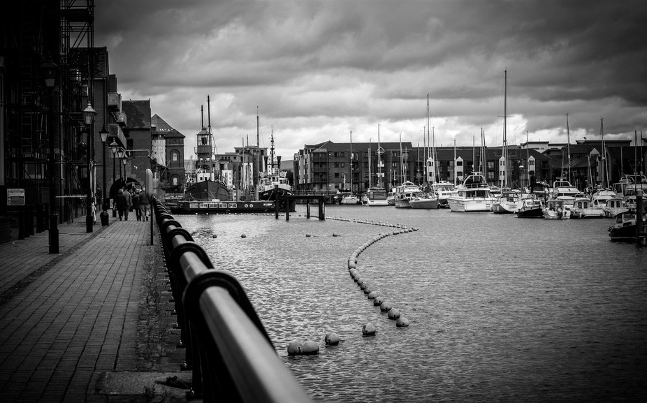 A black and white photograph of Swansea Marina under gathering clouds.