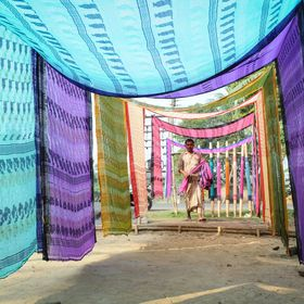 The man is weaver. He is drying newly finished cloth in  morning sunlight.