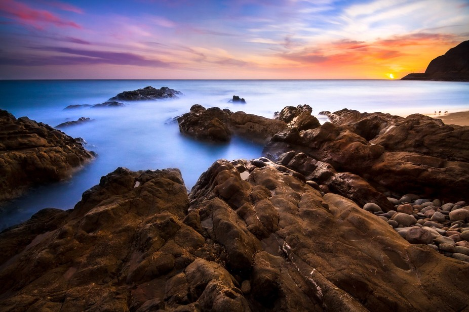 Soaking up the last rays of sunlight on a rocky shoreline in a long exposure seascape image taken...