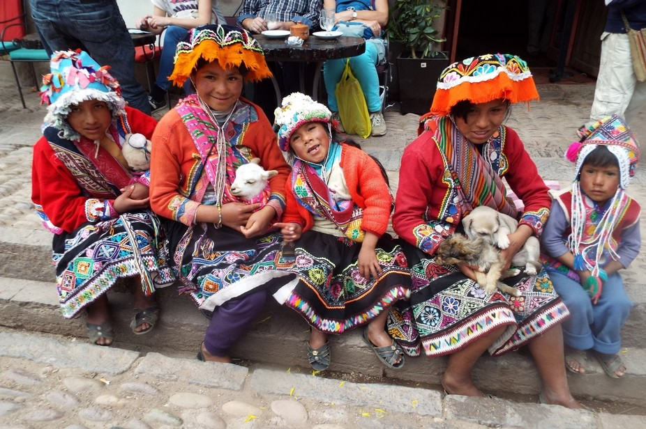 These adorable children with their baby goats and colorful clothing smiling for me while I took t...