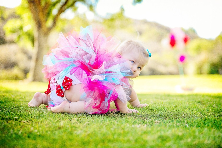 Tiny girl celebrates her first birthday  in  tutu style. she\'s enjoying a fun summer afternoon at...