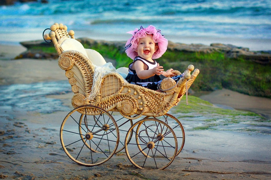 This young girl quite enjoys a ride in her buggy along the beach