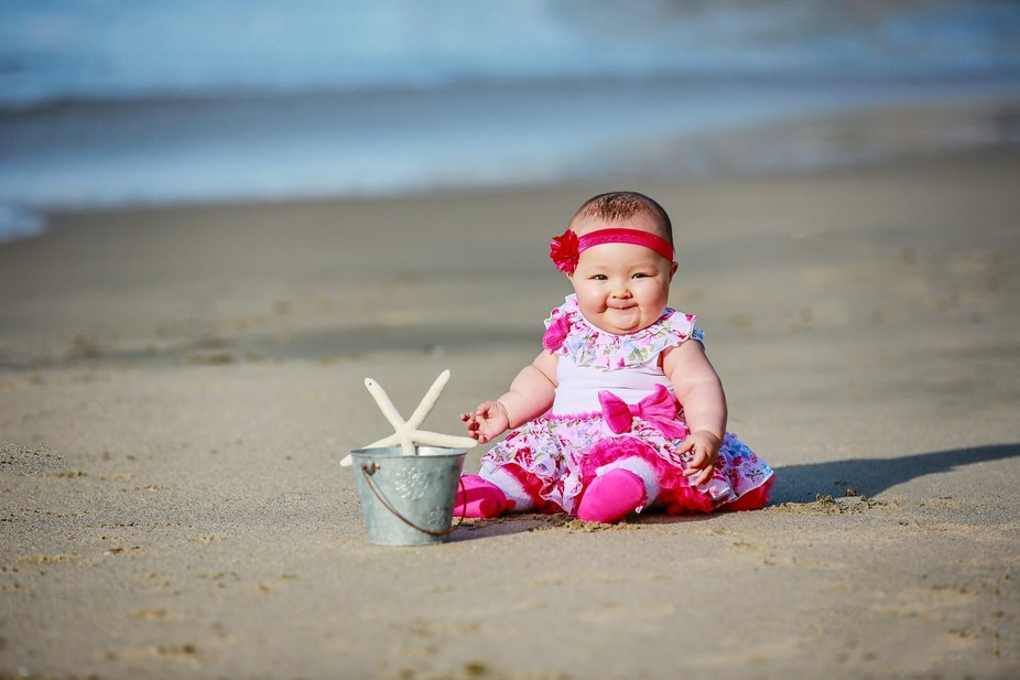 A baby girl sits with her pail and starfish on the beach in Laguna Beach