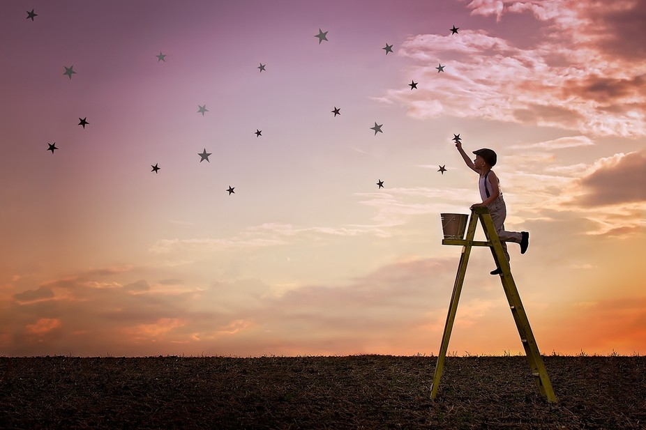 A child tends to his daily task of helping the stars fill up the night sky.