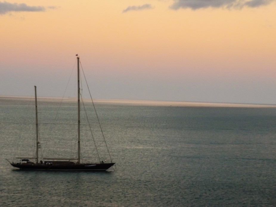 A boat sailing off the coast of Key West during sunrise. Such beautiful colors.