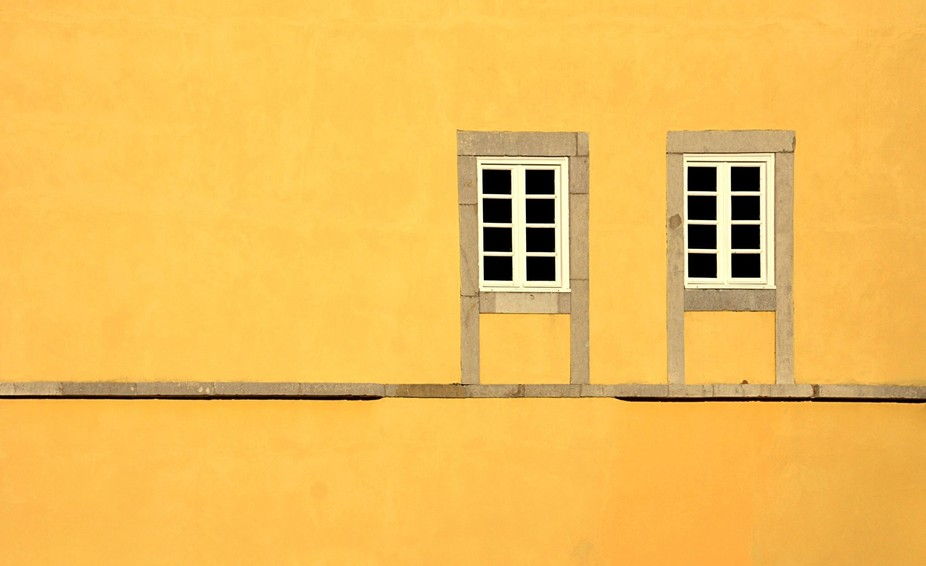 Windows on a yellow wall in Cascais, Portugal
