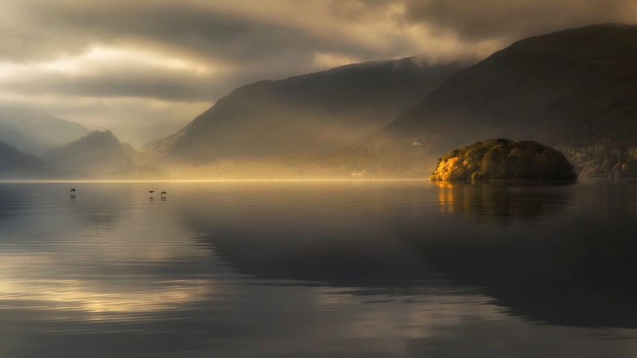 Sunrise light and mist over Derwentwater in the Lake District.