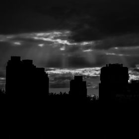 Silhouetted blocks of flats with a dramatic sky.