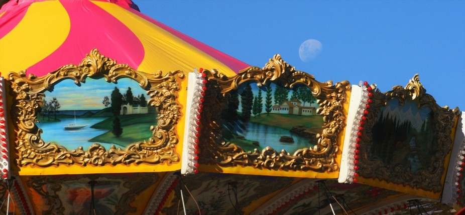 The frames of the carousel caught my eye with the moon it was as if the moon became part of all t...