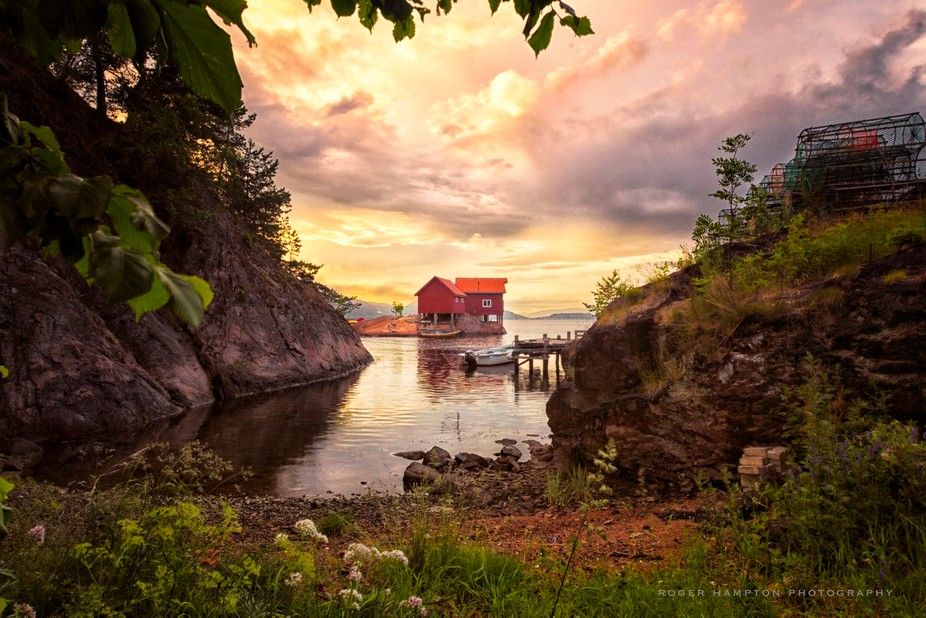 The photo depicts the well known fishing cabins on a little island in the fjord at Holmsbu. This ...