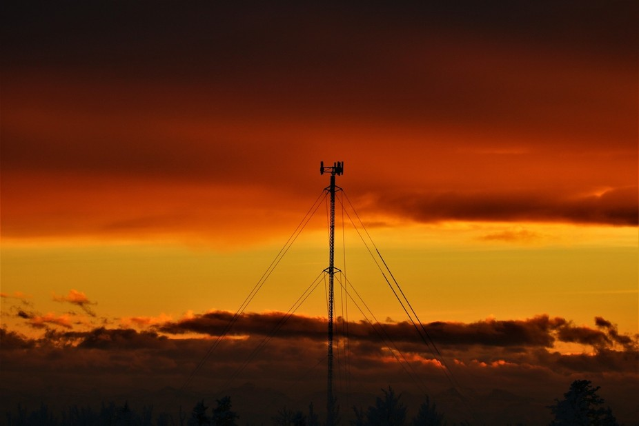 The radio tower presents itself in the center of the sunset sky