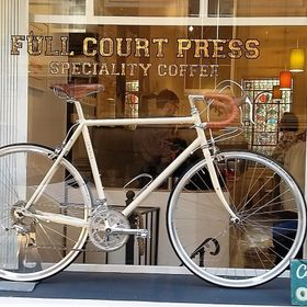 A cream bicycle displayed at a shop window.