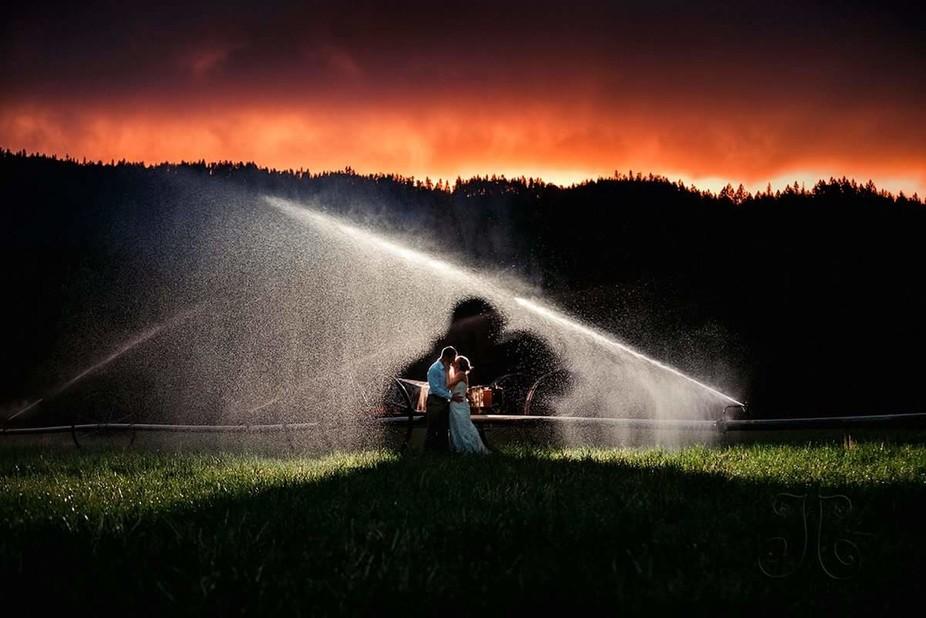 Backlight in bride and groom in the sprinklers.