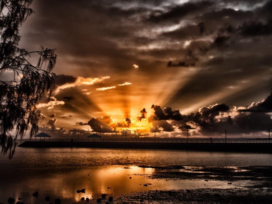 Sun Rising over Pandanus Beach,after early morning storm, Wynnum foreshore, Moreton Bay, Brisbane...