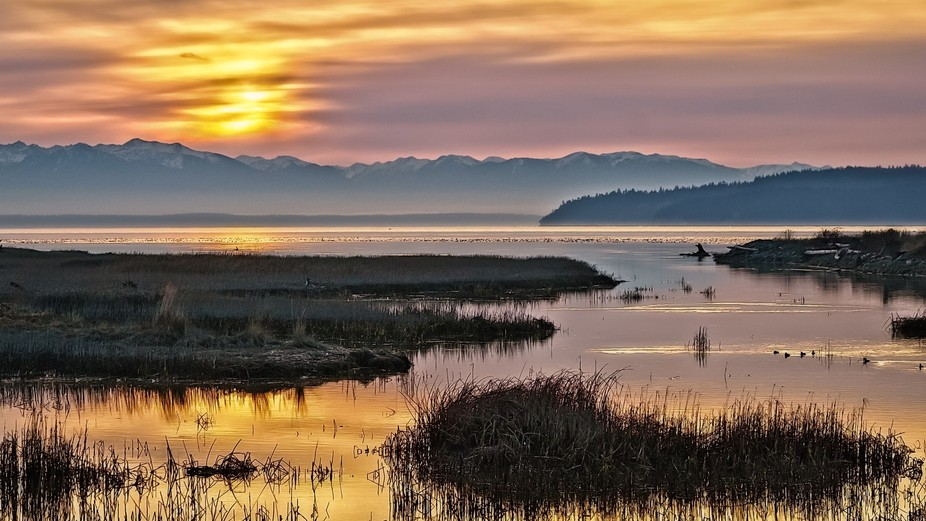 The sun is setting over Puget Sound in Washington State with the Olympic Mountains in the backgro...