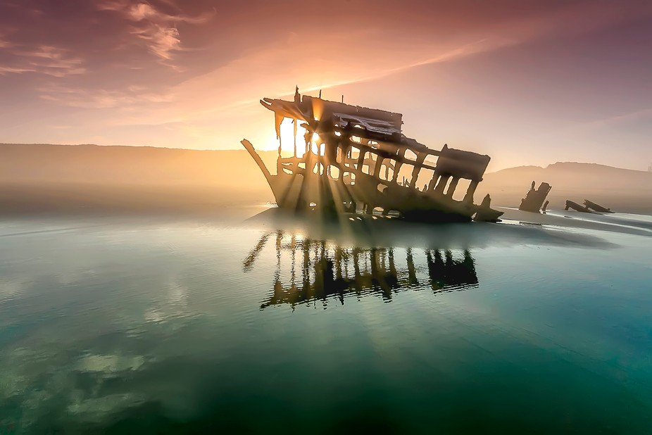 A shipwreck at sunrise on the beach in Oregon.