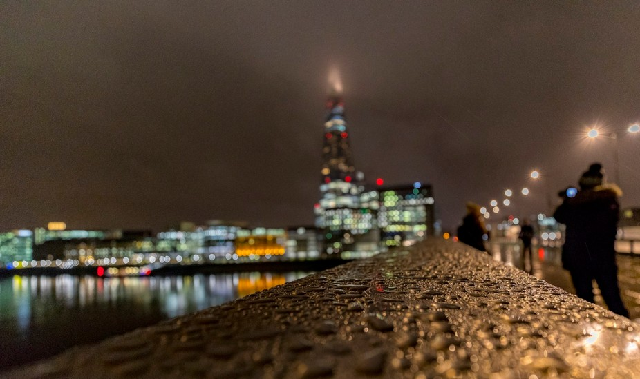 Rain falls on a wall that leads to the Shard building in London as commuters and tourists walk by.