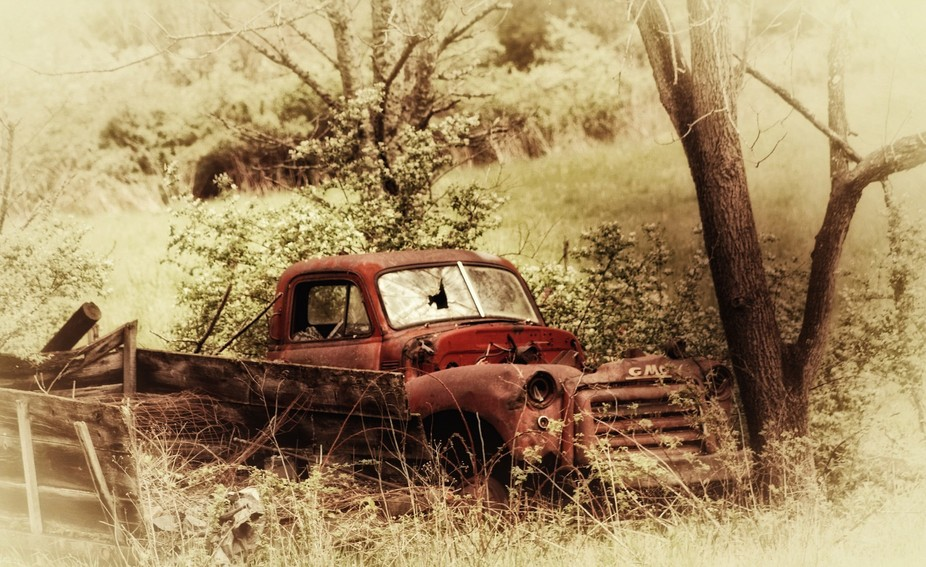 Old vehicle rusting away behind an old barn in Jumping Branch, WV