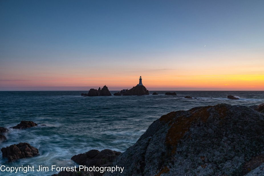 Sunset over the iconic La Corbiere Lighthouse St Ouens Bay Jersey
